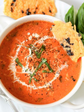 Tomato basil soup served in a white bowl with a parmesan crisp on the side